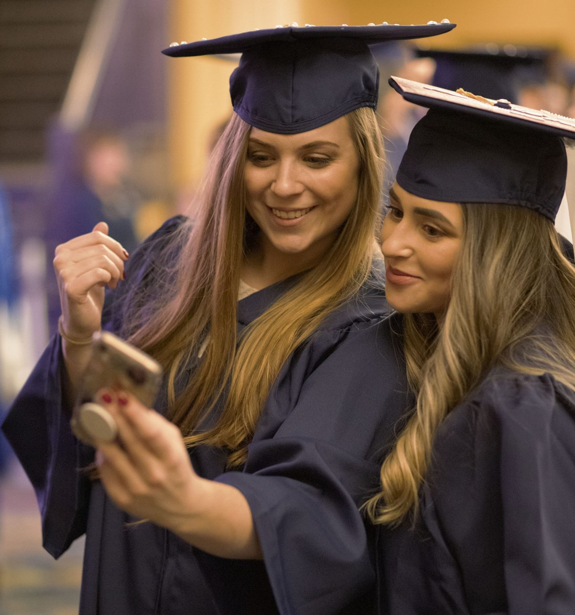 Two CEIN graduates take a selfie after their graduation ceremony.